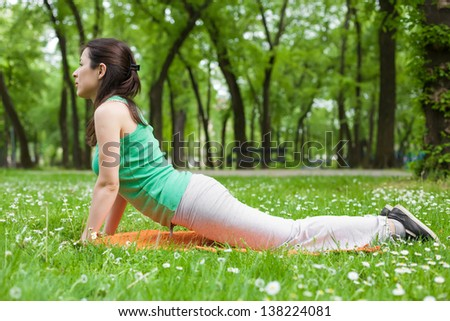 Young Woman Stretching in the Park - stock photo