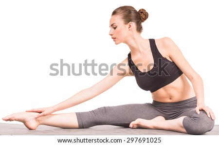 Young woman stretching in yoga position and looking on her leg at the studio. - stock photo