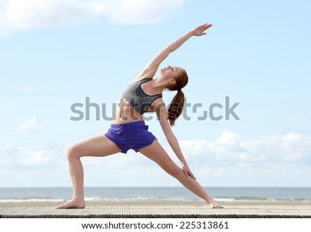 Young woman stretching in yoga position at the beach - stock photo