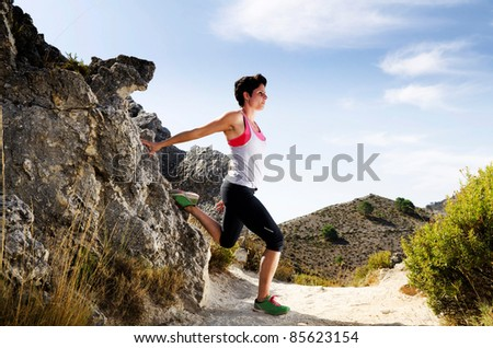 Young woman stretching on a dry mountain path. - stock photo