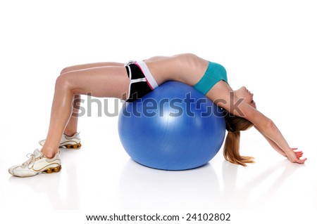 Young woman stretching on a fitness ball over a white background - stock photo
