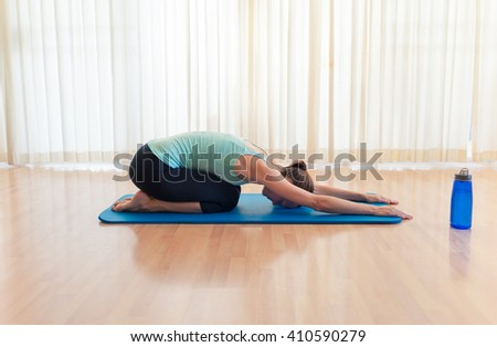 Young woman stretching on a yoga mat.  - stock photo