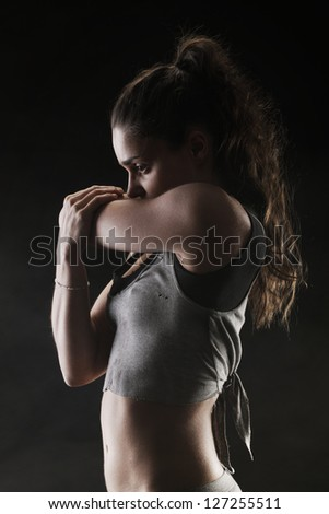 Young woman stretching on black background - stock photo
