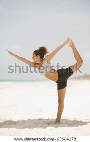 Young woman stretching on the beach - stock photo