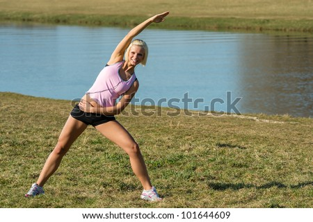 Young woman stretching outdoors before jogging workout river bank summer