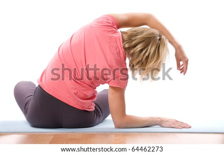 young woman stretching spine on a blue carpet over white - stock photo