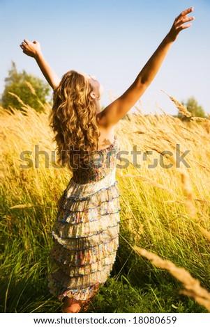 Young woman stretching up in a summer field. - stock photo