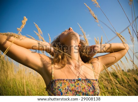 Young woman stretching up in a summer field. Wide angle view. - stock photo