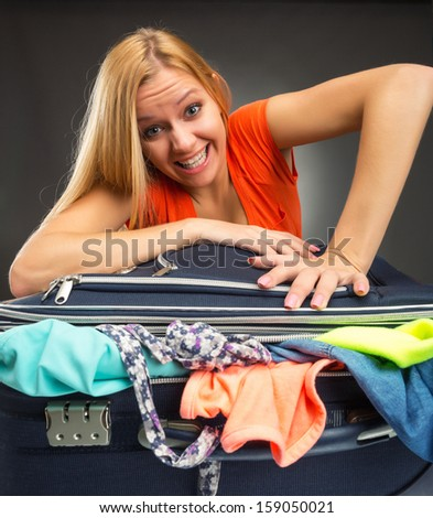 Young woman struggles to shut a suitcase full of clothing - stock photo