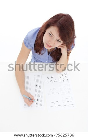 Young woman (student) filling IQ test - intelligence measuring concept. Focused on woman face, top view, white background. - stock photo
