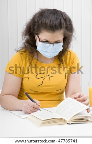 young woman student in the classroom in medical mask - stock photo