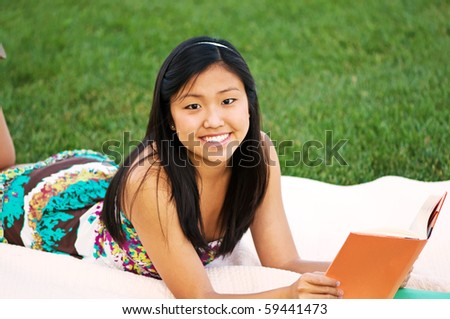 Young woman student reading on a blanket outdoors - stock photo