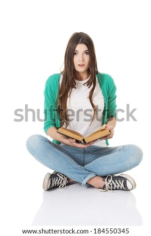 Young woman student sitting and reading a book. Isolated on white. - stock photo