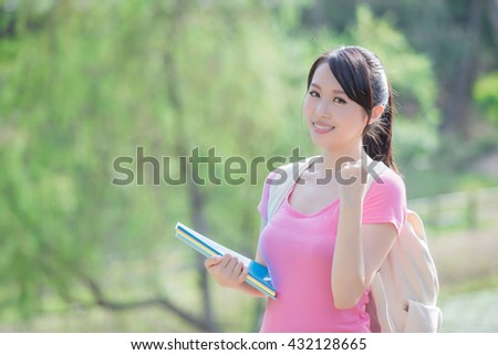young woman student smile to you and show a fist gesture. nature green background, asian beauty - stock photo