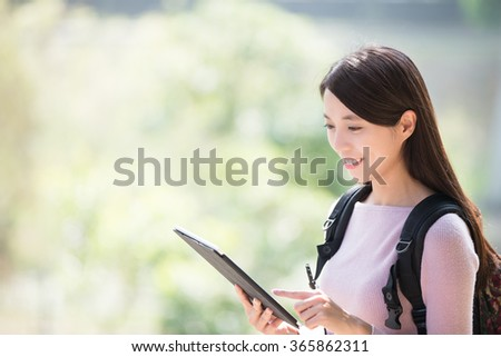 young woman student smile with digital tablet. nature green background, asian beauty - stock photo