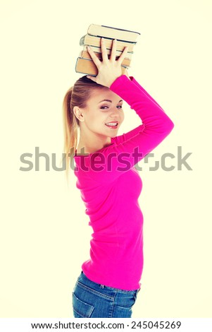 Young woman student with books on head.