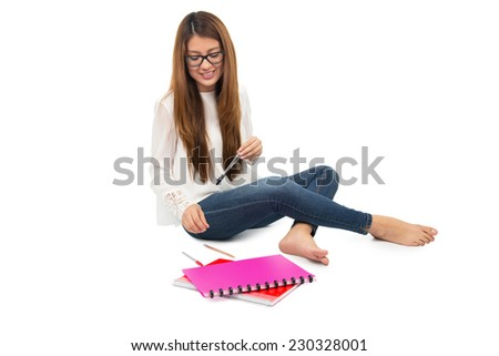 young woman student with glasses sitting on the floor - stock photo