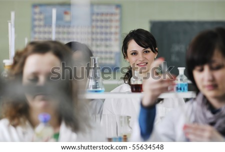 young woman students group in bright chemistry  lab - stock photo