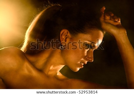 Young woman studio fashion portrait. Dark golden colors. - stock photo