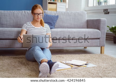 Young woman studying at home in the lounge sitting on the floor leaning against a sofa working with a laptop and class notes in binders - stock photo