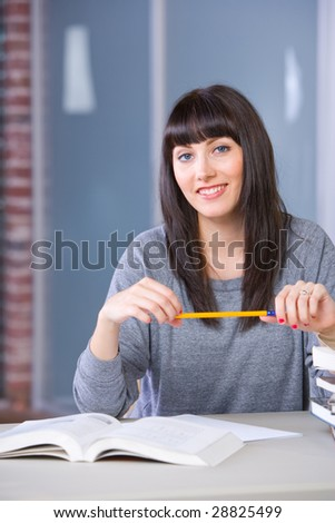 Young woman studying in a modern classroom - stock photo