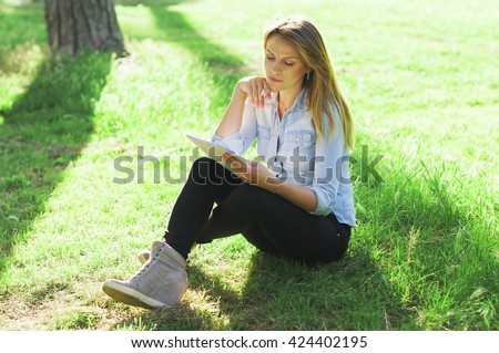Young woman studying in the park, selective focus