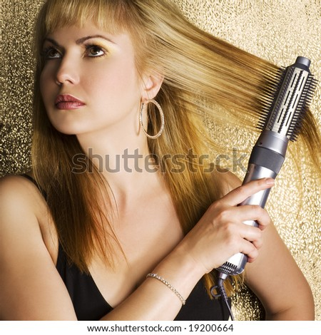 Young woman styling her long hair - stock photo