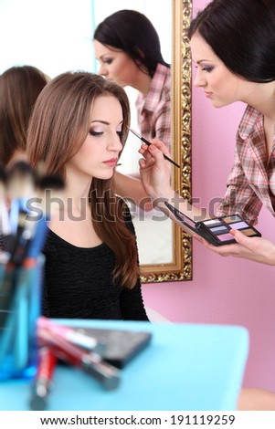 Young woman stylist doing makeup beautiful girl in beauty salon