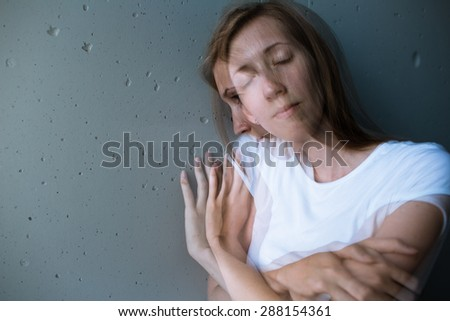 Young woman suffering from a severe depression/anxiety (color toned image; double exposure technique is used to convey the mood of unease, progression of the anxiety/depression) - stock photo