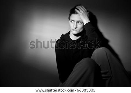 Young woman suffering from a severe depression/anxiety (color toned image; harsh lighting is used to convey the mood of unease) - stock photo