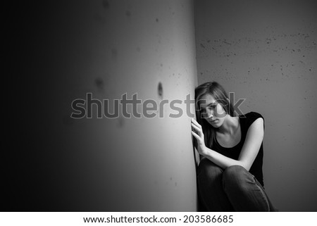 Young woman suffering from a severe depression (very harsh lighting is used on this shot to underline/convey the gloomy mood of the scene) - stock photo