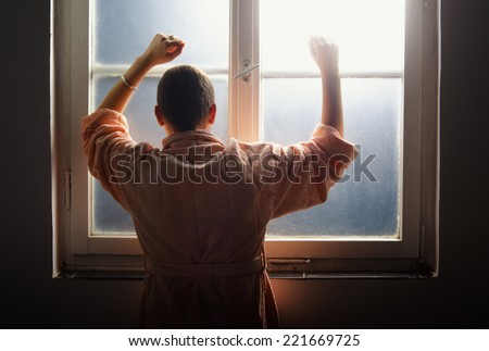 Young woman suffering from cancer leaning on the hospital window. - stock photo