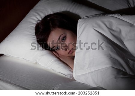 Young woman suffering from insomnia lying in bed at night - stock photo