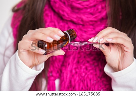 young woman suffering pouring syrup in spoon - stock photo