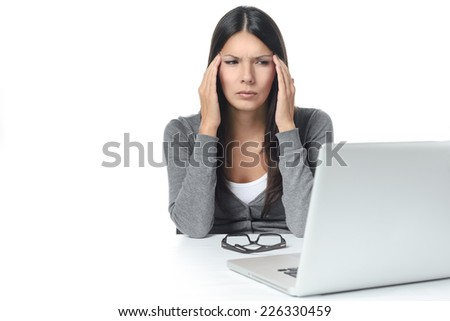Young Woman Suffers from headache or migraine Facing Laptop on the Table. isolated on White Background - stock photo