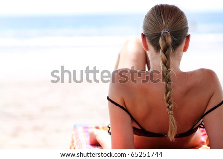 young woman sunbathes lying on chaise lounges - stock photo