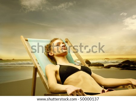 Young woman sunbathing at the seaside