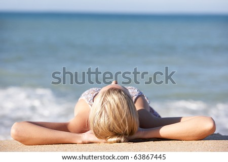 Young Woman Sunbathing On Beach - stock photo