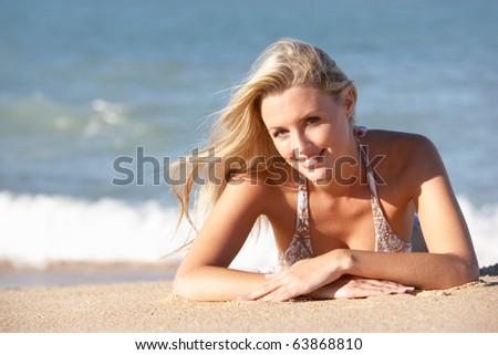 Young Woman Sunbathing On Beach - stock photo