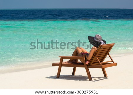 Young woman sunbathing on lounger at tropical beach