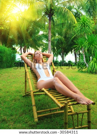 Young woman sunbathing on the chair in tropical garden - stock photo