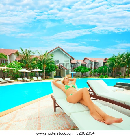 Young woman sunbathing on the chair near the swimming pool - stock photo