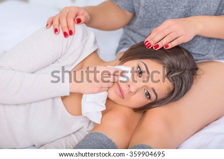 Young woman supporting her crying sister. - stock photo