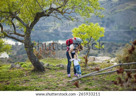 Young woman supporting son while he is making first steps outdoors - stock photo