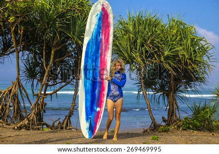 Young Woman Surfer Girl with Surfboard in Bali. - stock photo