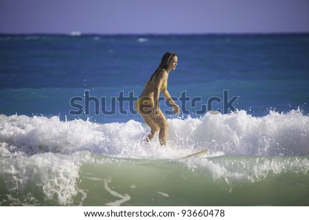 young woman surfing in hawaii - stock photo