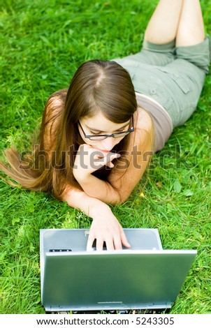 young woman surfing the internet outdoors on her laptop - stock photo