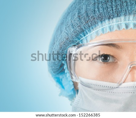 Young woman surgeon in cap, glasses and mask looks at camera, close-up - stock photo