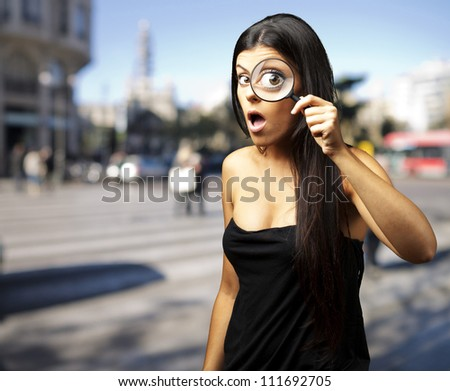 Young woman surprised looking through a magnifying glass at city - stock photo