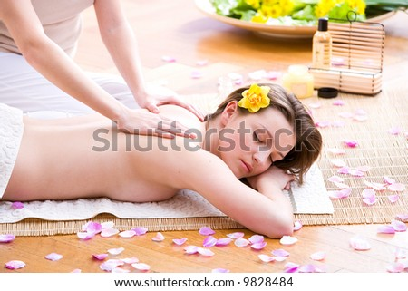 young woman surrounded by petals is getting a massage - stock photo